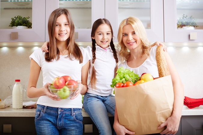 happy mother and two daughters looking at camera in the kitchen